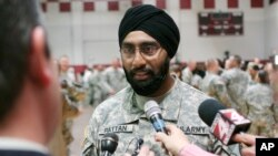 FILE - U.S. Army Capt. Tejdeep Singh Rattan speaks to journalists at Fort Sam Houston in San Antonio, March 22, 2010. Rattan was the first Sikh allowed to complete officer basic training while wearing the traditional turban and full beard since the Army altered its dress code. The New York City police have now adopted a similar dress policy.