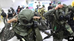 "South Korean army soldiers put on gas masks during South Korea-U.S. joint military exercise, ""Ulchi Focus Lens,"" at a subway station in Seoul, South Korea, Aug. 19, 2013."