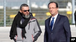 L'ex-otage Marc Feret, à gauche, est accueilli après sa libération par le président François Hollande en France, à la base aérienne militaire de Villacoublay, dans la périphérie de Paris, 30 octobre 2013.