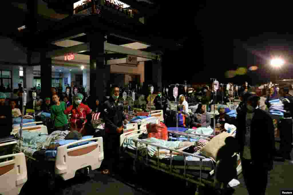 Patients are seen outside a government hospital near Denpasar, Bali, Indonesia, following a strong earthquake nearby Lombok island.