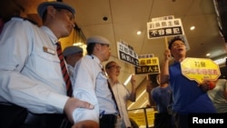 Protesters chant slogans in front of security guards inside building where Japanese Consulate is located in Hong Kong, August 15, 2012.