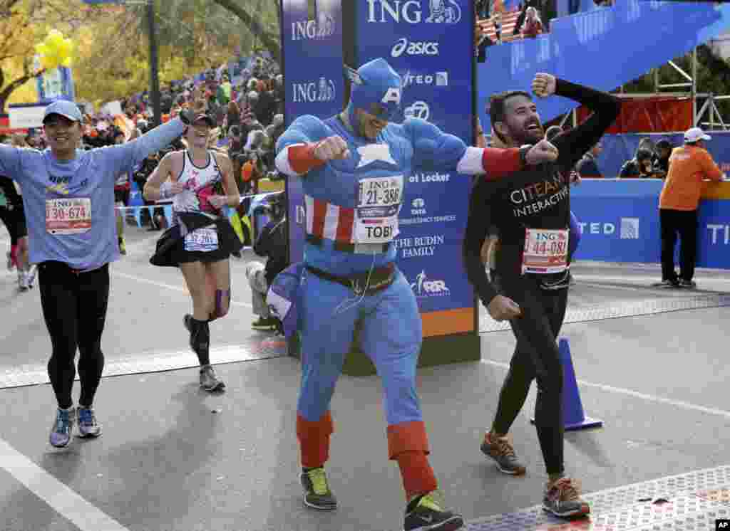 Runners, including a man wearing a Captain America costume, react as they cross the finish line after completing the New York City marathon, Nov. 3, 2013.