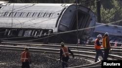 Para petugas memeriksa lokasi kecelakaan kereta Amtrak yang keluar dari jalurnya di Philadelphia hari Selasa (12/5) malam.