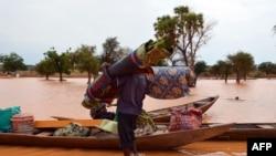 Un homme transporte ses affaires dans une pirogue le 5 septembre 2013. Il quitte un quartier de Niamey où les inondations ont fait 26 morts et 75 347 sinistrés. Elles ont aussi détruit 13 000 ha de terres agricoles et causé plusieurs dégâts. PHOTO AFP / BOUREIMA HAMA