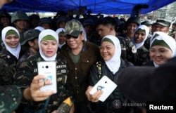 Philippine President Rodrigo Duterte, center, poses for a picture with female soldiers during his visit at Bangolo town in Marawi city, southern Philippines, Oct. 17, 2017.