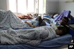 Injured men receive treatment at a hospital after a clash between Taliban and security forces in Kunduz province, Afghanistan, April 13, 2019.