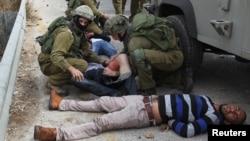 Binh sĩ Israel chữa trị cho những người Palestine ném đá bị thương sau khi bị lực lượng Israel bắn trả trong vụ đụng đột tại thị trấn Beil El, ngày 7/10/2015.