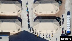 "Immigrant children, many of whom have been separated from their parents under a new ""zero tolerance"" policy by the Trump administration, are shown walking in single file between tents in their compound next to the Mexican border in Tornillo, Texas, June 18, 2018."
