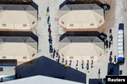 "FILE - Immigrant children, many of whom have been separated from their parents under a new ""zero tolerance"" policy by the Trump administration, are shown walking in single file between tents in their compound next to the Mexican border in Tornillo, Texas, U.S.,"