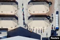 """Niños inmigrantes, muchos de los cuales han sido separados de sus padres bajo una nueva política de """"tolerancia cero"""" de la administración Trump, se muestran caminando en fila india entre tiendas de campaña en su recinto junto a la frontera con México en Tornillo, Texas, EE.UU."""