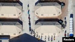 """Anak-anak imigran, banyak di antaranya yang telah dipisahkan dari orang tuanya di bawah kebijakan baru """"tanpa toleransi"""" pemerintahan Trump, tampak berjalan dalam satu barisan di antara tenda-tenda di komplek dekat perbatasan Meksiko di Tornillor, Texas, AS, 18 Juni 2018 (foto: REUTERS/Mike Blake)"""