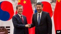 지난 2017년 12월 문재인 한국 대통령과 시진핑 중국 국가주석이 베이징 인민대회당에서 열린 서명식에서 악수하고 있다.