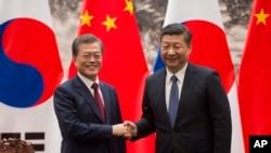 Presiden Korea Selatan Moon Jae-in (kiri) dan Presiden China Xi Jinping berjabat tangan pada akhir upacara penandatanganan kerjasama di Balai Besar Rakyat China di Beijing, Kamis, 14 Desember 2017.