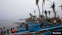 FILE - Homeless typhoon victims gather near their new fishing boats given by a religious organization along a coastal village devastated by super Typhoon Haiyan in Tacloban city, central Philippines.