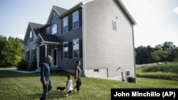Joyce Lilly, right, holds her granddaughter Paige's hand alongside her husband, Anil, and dog Max at their new home, Tuesday, July 21, 2020, in Washingtonville, New York. (AP Photo/John Minchillo)