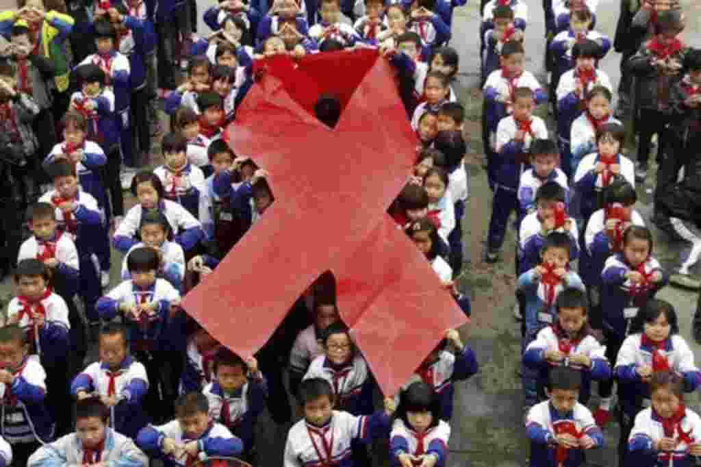 Los estudiantes de primaria presentan lazos en un evento en la víspera del Día Mundial del SIDA en Wuyuan, en la provincia china de Jiangxi. China tendrá cerca de 780.000 personas infectadas con el virus del SIDA a finales de 2011.