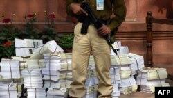"""Nhân viên an ninh Ấn Độ đứng canh gác bên cạnh những bản sao của báo cáo """"Điều tra kinh tế 2014-2015"""" tại Tòa nhà Quốc hội ở New Delhi, ngày 27/2/2015."""