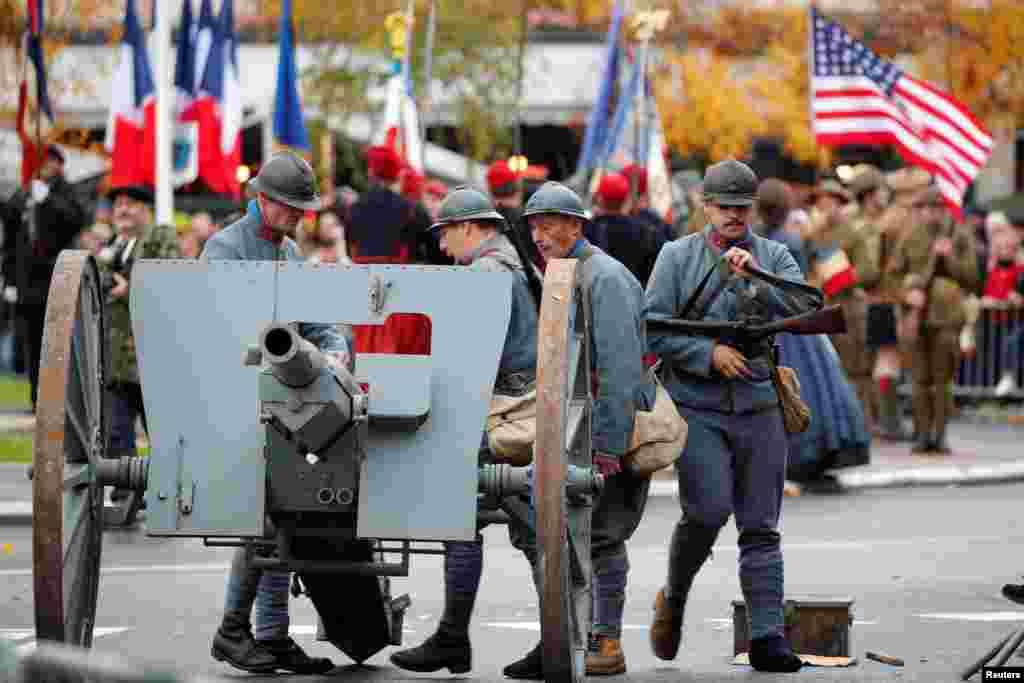 Entusiastas históricos vestidos de soldados franceses preparam-se para disparar um canhão, durante a cerimónia do Dia do Armistício, em Epernay, França, 11 Novembro, 2018.