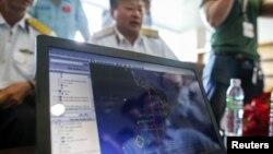 Các nhân viên sắp thực hiện việc tìm kiếm chiếc máy bay bị mất tích xem đường bay của máy bay MH370 trên màn hình