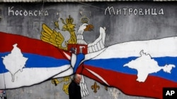 FILE - A man walks by graffiti that shows Serbian, left, and Russian flags with maps of Kosovo and Crimea in northern, Serb-dominated part of ethnically divided town of Mitrovica, Kosovo, Dec. 15, 2018.