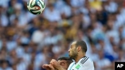Argentina's Javier Mascherano leaps to head the ball past Iran's Ashkan Dejagah during the group F World Cup soccer match between Argentina and Iran at the Mineirao Stadium in Belo Horizonte, Brazil, Saturday, June 21, 2014.
