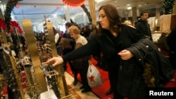 FILE - Shoppers browse at a Macy's store in New York.