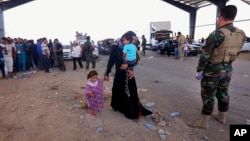 A Kurdish policeman stands guard while refugees fleeing Mosul head to the self-ruled northern Kurdish region in Irbil, Iraq, June 10, 2014.