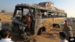 Onlookers gather around and inside the wreckage of a passenger bus that was destroyed by fire after colliding with a tanker truck on a highway about 50 kilometers (31 miles) outside of Karachi, Pakistan, Jan. 11, 2015.