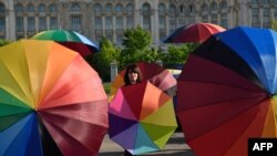 People hold rainbow umbrellas to celebrate International Day Against Homophobia, Biphobia and Transphobia in the front of the Romanian Parliament building in Bucharest, May 17, 2016.