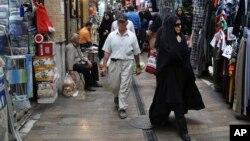 FILE - Iranians walk through a bazaar in Tajrish northern Tehran, Iran, July 7, 2015.