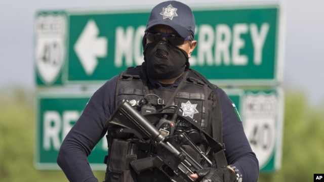 Mexico police guard an area where dozens of bodies were found