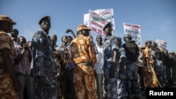 Policemen stand guard as protesters representing regions along the border with Sudan gather outside of the Parliament building in Juba, South Sudan, against a recently signed agreement between Sudan and South Sudan, October 15, 2012.
