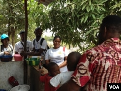 Zero Ebola Campaign volunteers, including Mary Kargbo (center), talk to residents in Freetown, Sierra Leone, March 27, 2015. ( Nina Devries/VOA)