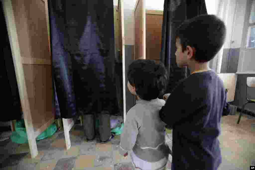 Boys wait outside a voting booth for their father during parliamentary elections at a polling station in Boumerdes, east of Algiers.