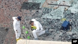 Two men in hazardous materials suits investigate the scene at the first bombing on Boylston Street near the finish line of the 2013 Boston Marathon, a day after two blasts killed three and injured more than 170 people, in Boston, April 16, 2013.