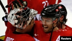 Canada's Shea Weber (R) celebrates with goalie Carey Price after Canada won their men's ice hockey semi-final game against Team USA at the 2014 Sochi Winter Olympic Games, February 21, 2014.