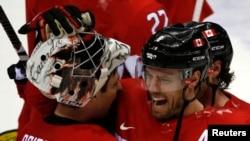 2014年2月21日在索契冬奥会举行的冰球半决赛中,加拿大男子队以1比0击败美国队后,加拿大冰球队员欣喜若狂。
