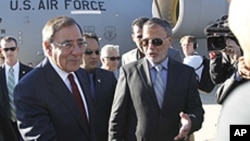 U.S. Secretary of Defense Leon Panetta greets members of the Libyan delegation on the tarmac during his arrival in Tripol, Saturday, Dec., 17, 2011.