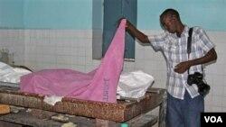 Seorang wartawan Somalia memeriksa jenazah rekannya yang ditembak tewas di ibukota Mogadishu (18/12). Bentrokan antara kelompok militan al-Shabab dan pasukan pemerintah Somalia membuat situasi di Mogadishu terus memburuk.