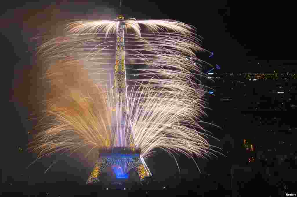 """Fireworks light the sky near the Eiffel Tower in a show called """"Guerre et Paix"""" (War and Peace) as part of events to mark the centenary of the First World War and to end the traditional Bastille Day celebrations in Paris, July 14, 2014."""