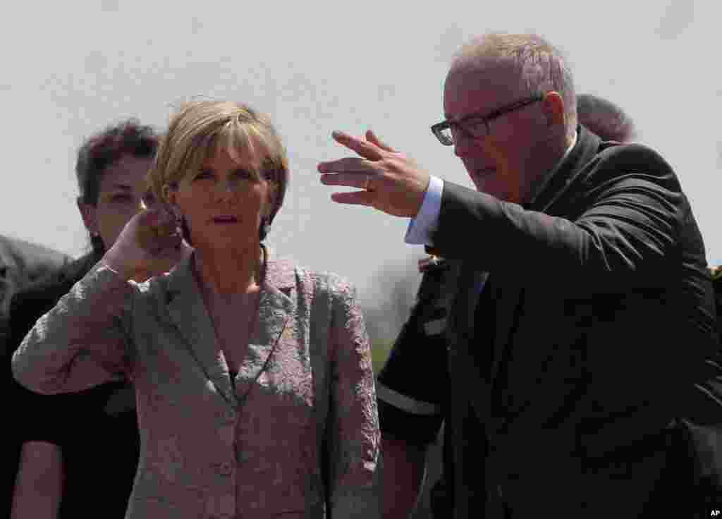 Netherlands Foreign Minister Frans Timmermans, right, and Australian Foreign Minister Julie Bishop speak to each other as a Dutch military cargo plane with bodies of some of the passengers of the downed Malaysia Airlines jetliner leaves Ukraine, July 25, 2014.