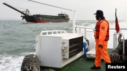 A Taiwanese coast guard looks at a sand-dredging ship with Chinese flag in the waters off the Taiwan-controlled Matsu islands, January 28, 2021. (REUTERS/Ann Wang)