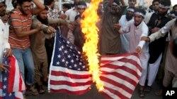 塔利班領導人哈基姆拉.馬蘇德的支持者在巴基斯坦街頭燒燬美國國旗,抗議美國在巴基斯坦使用無人機轟炸。