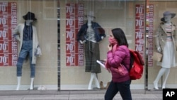 A shopper walks past a clothing shop display on a shopping street in Tokyo Monday, Feb. 15, 2016.