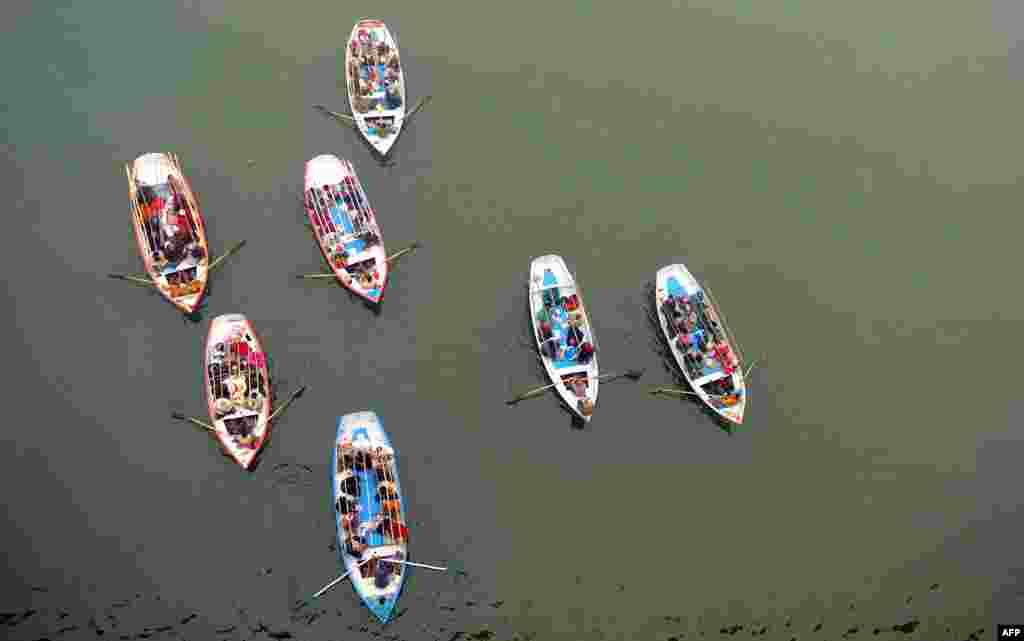 Indian Hindu pilgrims travel on boats to take a holy dip at Sangam, the confluence of the Rivers Ganges, Yamuna and the mythical Saraswati during the Maha Kumbh Mela in Allahabad, India.