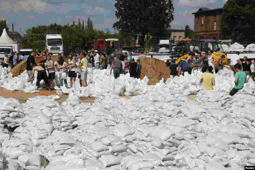 10일 독일 위튼버그 도시 엘베 강 수위가 평상시보다 5미터 넘게 불어난 가운데, 자원봉사자들이 샌드백을 옮기고 있다.