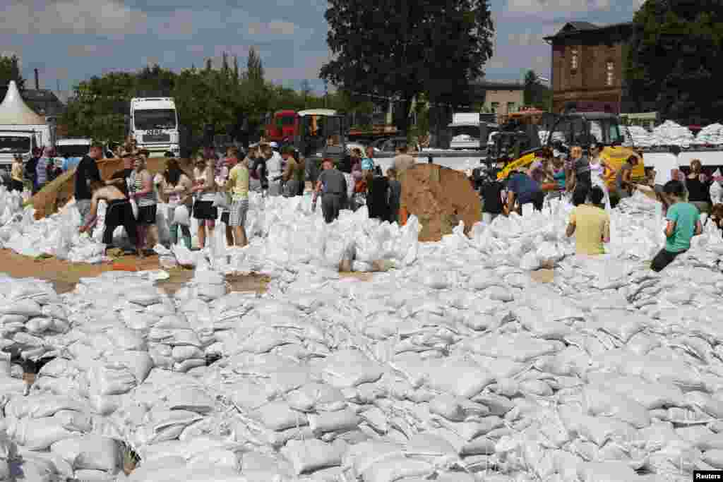 Volunteers carry sandbags to make a barrier near the river Elbe in the town of Wittenberge, Germany, June 10, 2013.