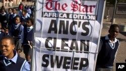 Des élèves arborent une pancarte du Congrès national africain (ANC), le parti de Jacob Zuma.