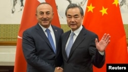 Chinese Foreign Minister Wang Yi, right, shakes hands with Turkish Foreign Minister Mevlut Cavusoglu during their meeting at Diaoyutai State Guesthouse in Beijing, China, Aug. 3, 2017.