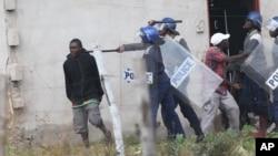 FILE: Armed Zimbabwean police clash with rioters in Harare, Monday, July 4, 2016. (AP Photo/Tsvangirayi Mukwazhi)